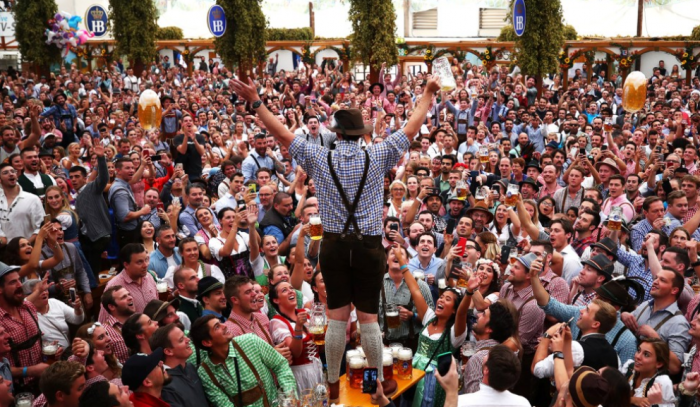 Man in lederhosen stands before an Oktoberfest crowd