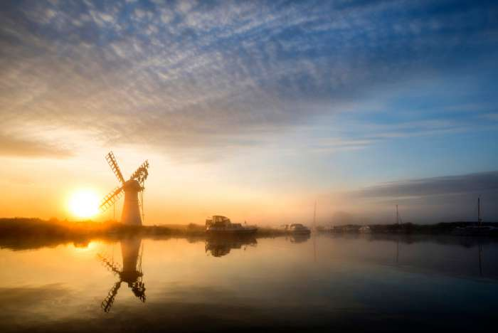 A windmill on The Broads during a misty sunrise