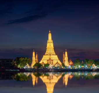 Wat Arun temple illuminated by lights against night sky