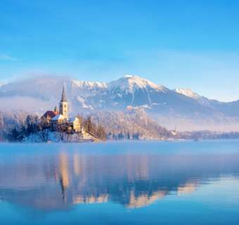 Lake Bled on a sunny winter morning with snow on mountains