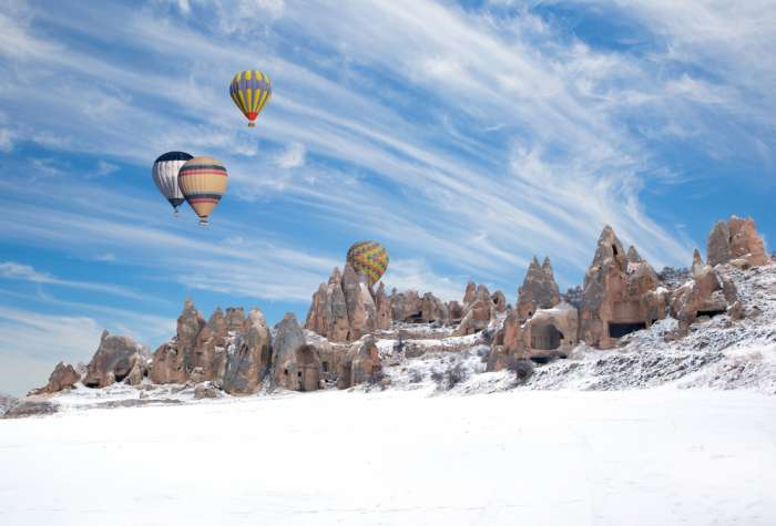 Hot air balloons flying over Cappadocia in the snow