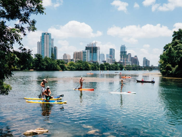 Paddle boarders on Lady Bird Lake in front of Austin skyline