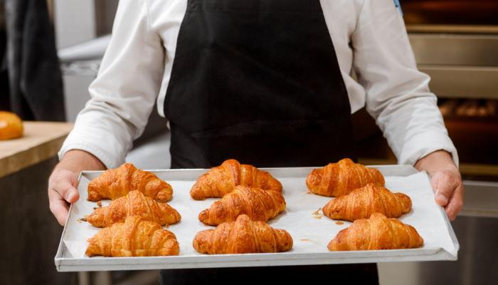 Baker holding tray of freshly-baked croissants