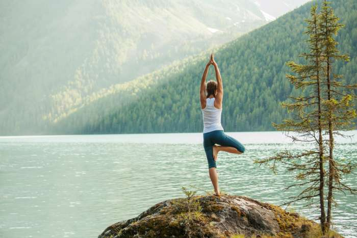 Young woman practises yoga on the edge of a lake