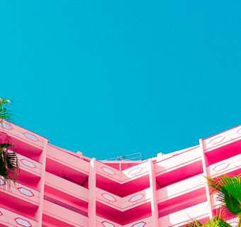 Palm trees in front of a pink hotel