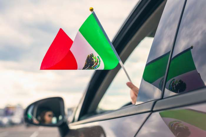 Hand waving a small Mexican flag out a car window