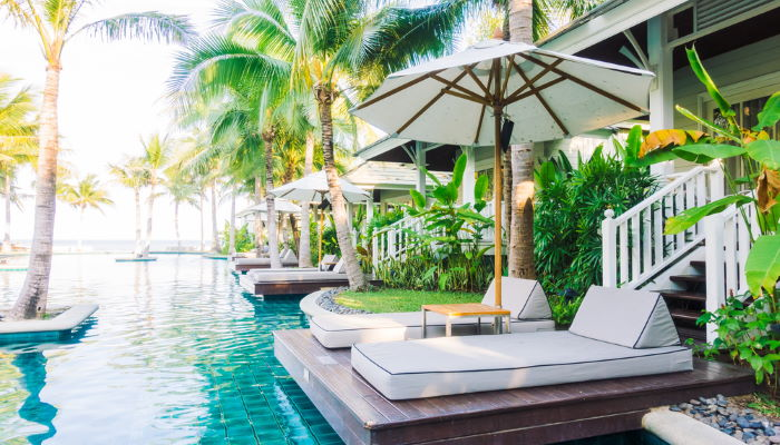 Balinese beds next to a tropical hotel's swimming pool