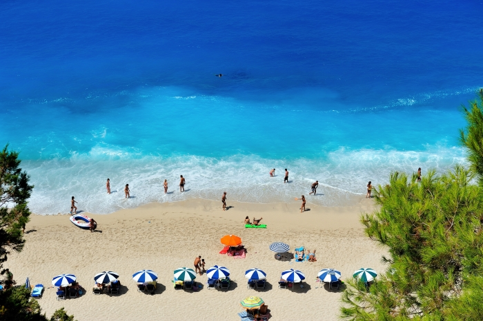 Beach in height of summer with blue sea and striped umbrellas