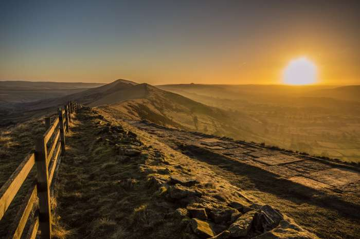 Landscape scene from the Pennine Way, with the sun rising over distant hills