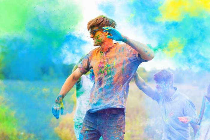 A young man dances at Holi, with blue and yellow paint in the air