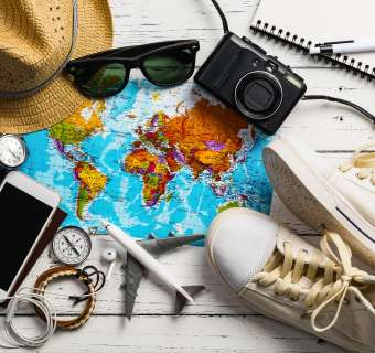 Flatlay of travel essentials, including mobile, hat, shoes and a map