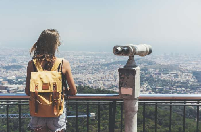 A young woman looks out over a city with binoculars next to her