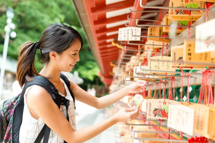 A female tourist hangs wooden prayer cards at a Japanese shrine