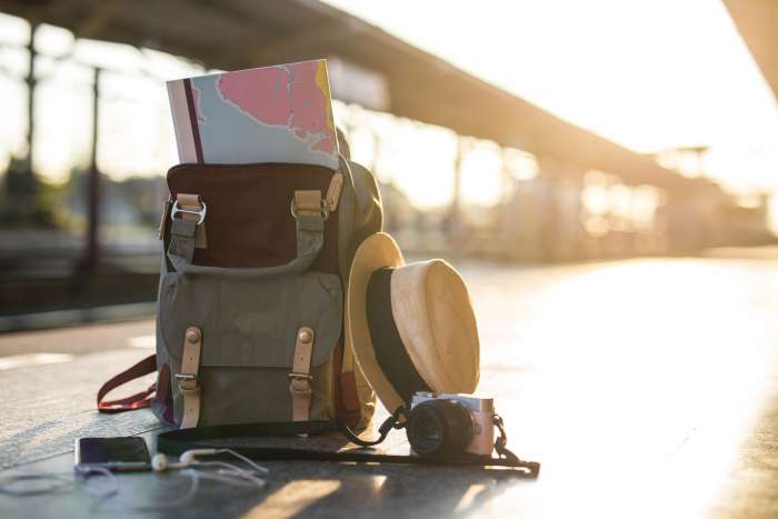 A canvas backpack with a map, hat and camera