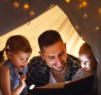 Father and children reading book in homemade den