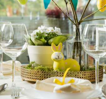 Easter dinner table set up with wine glasses and egg and bunny ornaments