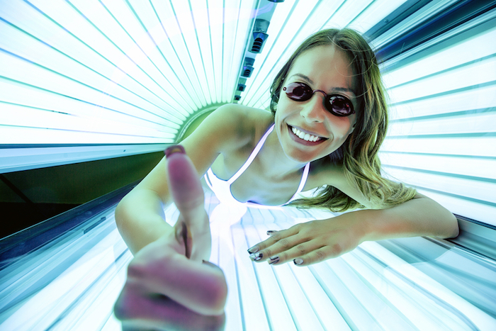 Woman with thumbs up while sunbedding