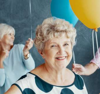 elderly people laughing with balloons