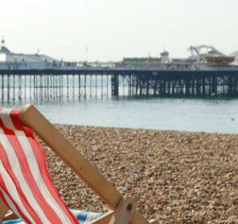 deckchairs on the beach with pier in background