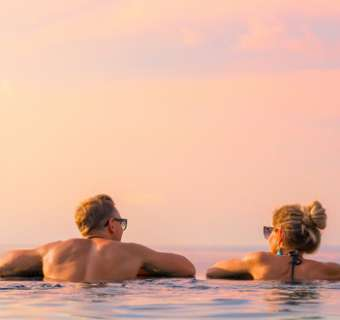 Romantic couple looking at beautiful sunset in luxury infinity pool