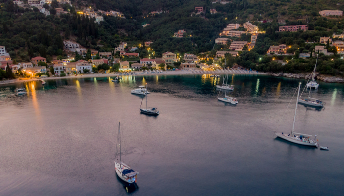 Picture of Corfu's coastline at dusk, featuring boats and buildings